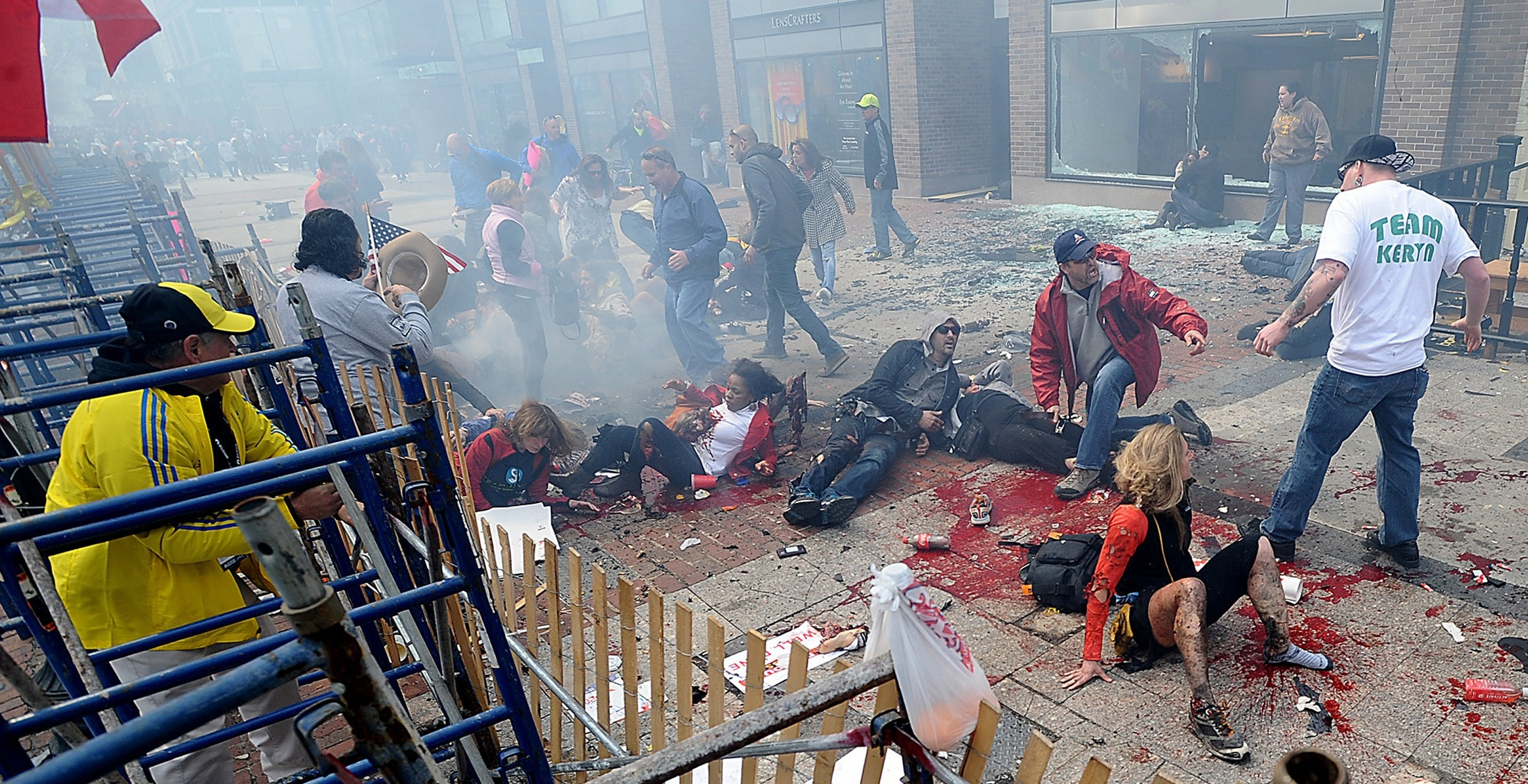 Wounded spectators lie injured following an explosion at the Boston Marathon